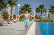 Caucasian boy running along swimming pool at resort. He is moving towards camera and holding arms wide open.
