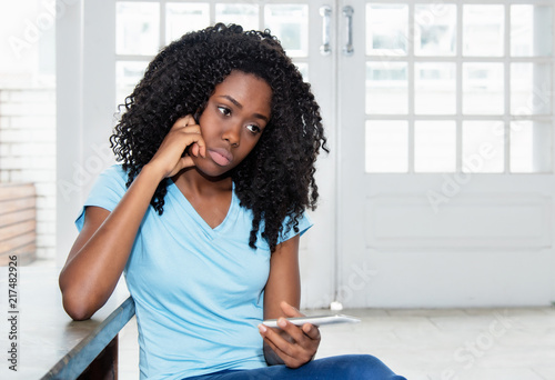 Sad and lonely african american woman waiting for message