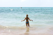 Slim girl with long hair goes to the sea by sandy beach
