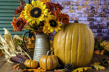 Fall Scene Of Orange Pumpkins Autumn Leaves Pine Cones Dried Corn With Sunflower Bouquet In Metal Pitcher On Wood Table