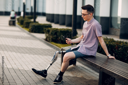 Photo  Disabled young man with foot prosthesis sitting and hold mobile phone outdoor