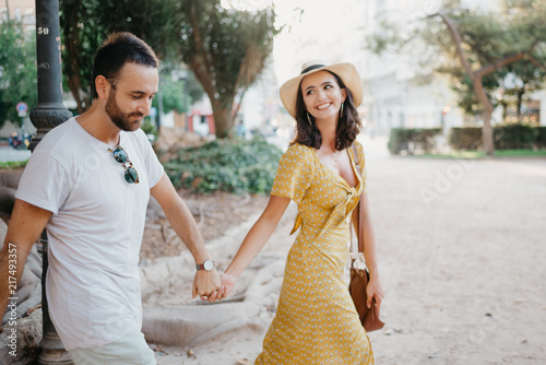 Photo sur Toile Attraction parc Beautiful young brunette woman with her boyfriend with beard walking holding hands under the giant tree in the city park in Spain in the evening. Intimate photo