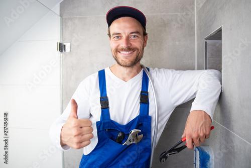Fototapeta Installateur sympathisch Lachend bei der Arbeit