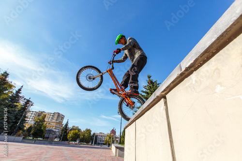 BMX cyclist made tricks on street, pro rider trainong