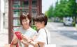 東京・観光イメージ・渋谷・ガイドブックを見ながら話す女子2人