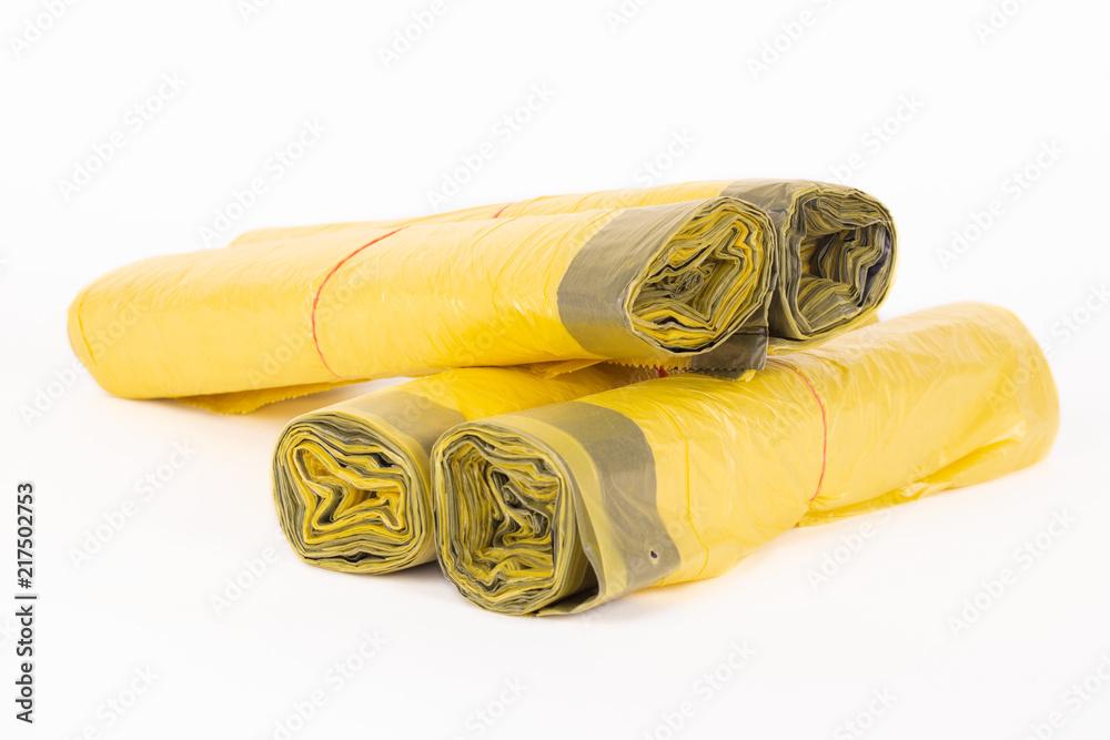Fototapeta Rolls of yellow trash bags on white background