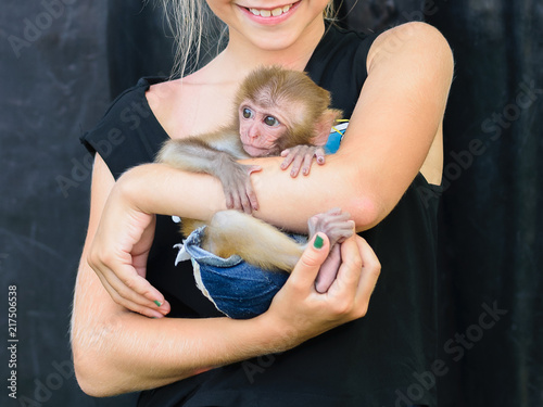 Foto op Plexiglas Aap The girl carefully holds a small monkey on her hands.