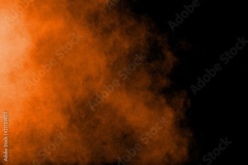 Fototapeta Abstract orange powder explosion on black  background. Freeze motion of orange  dust particles splash. obraz