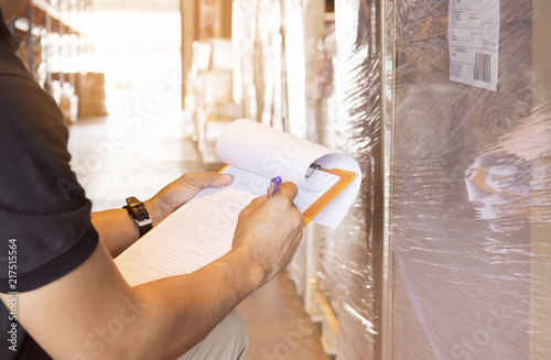 Valokuva  Worker are holding a clipboard writing with checking the product in warehouse