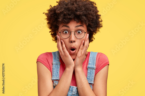 Fototapeta Photo of surprised African American female touches cheeks, opens eyes and mouth widely, dressed in casual clothes, isolated over yellow background. Shocked mixed race woman poses alone indoor. obraz na płótnie