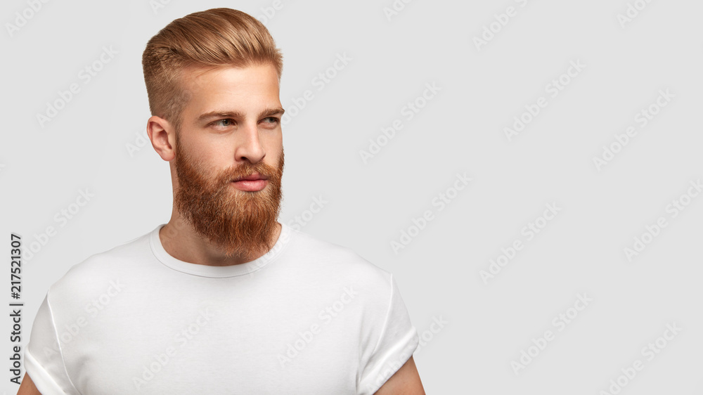 Fototapety, obrazy: Serious thoughtful male with ginger beard, dressed casually, focused somewhere, isolated over white background with free space on right for your advertising content. Pensive red haired hipster