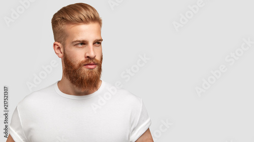 Serious thoughtful male with ginger beard, dressed casually, focused somewhere, isolated over white background with free space on right for your advertising content. Pensive red haired hipster