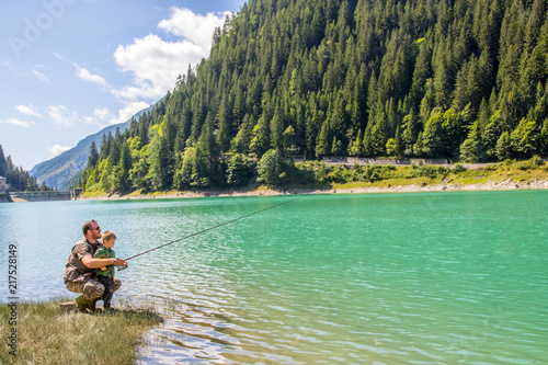 happy father and son fishing together on a mountain lake