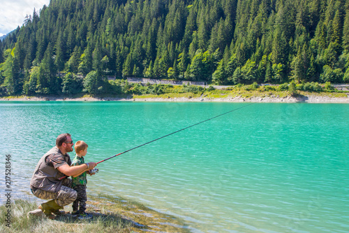 Poster Peche happy father and son fishing together on a mountain lake
