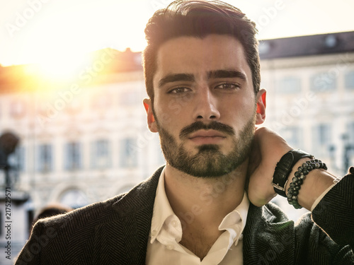 Stampa su Tela  Handsome serious businessman standing outside in elegant European city center, T