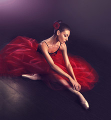 Ballerina. Young graceful woman ballet dancer, dressed in professional outfit, shoes and red weightless skirt is demonstrating dancing skill. Beauty of classic ballet dance.