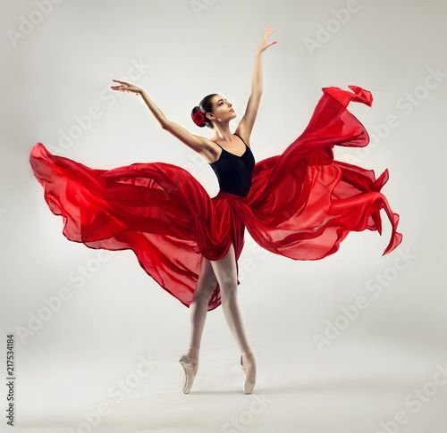 plakat Ballerina. Young graceful woman ballet dancer, dressed in professional outfit, shoes and red weightless skirt is demonstrating dancing skill. Beauty of classic ballet dance.