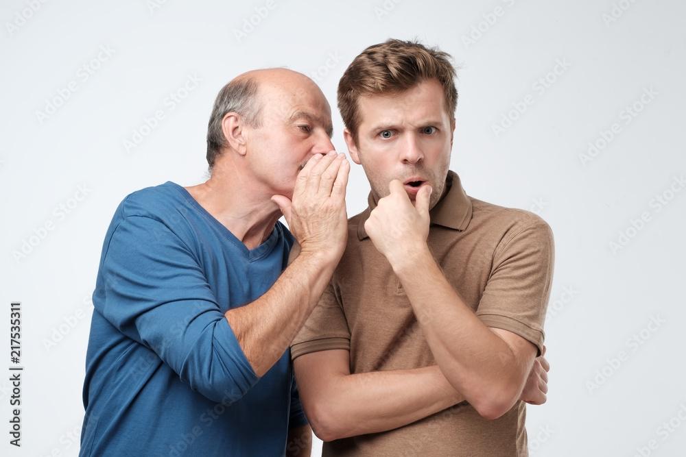 Fototapety, obrazy: Senior man sharing secret or whispering gossips into his son ear. Telling family secret concept
