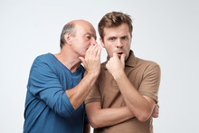 Senior Man Sharing Secret Or Whispering Gossips Into His Son Ear. Telling Family Secret Concept