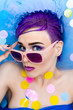 Portrait of young woman female girl / fashion luxury model with purple hair and bright makeup relaxing in bath with confetti and pink sunglasses. Organic skin care, beauty and body care concept.