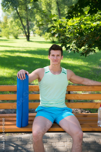 Relax concept. Athlete relax on bench in park. Sportsman relax after yoga training. Relax and enjoy life