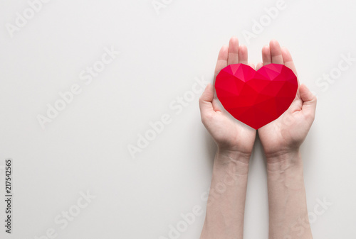Obraz na płótnie Red polygonal heart in female hands on white background