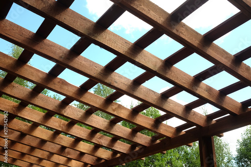 Fototapeta Top of brown wooden pergola on sunny summer day side view outdoor
