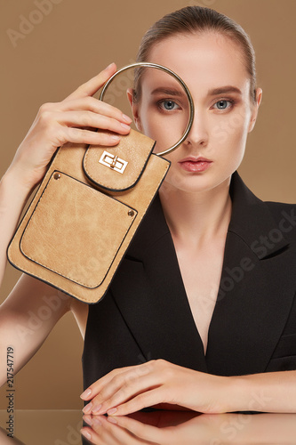 Fotografia  A studio portrait of a chic young lady sporting slicked back hair and looking at the camera through the metal o-ring handle of her beige leather purse