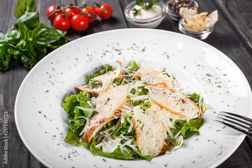 Deurstickers Klaar gerecht Salad with chicken breast, parmesan cheese, croutons, mixed greens, lettuce on wooden background. Healthy food