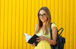 Leinwanddruck Bild Pretty smiley girl student with book wearing funny toy round glasses and suitcase over yellow background