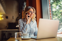 Portrait Of Young Business Woman With Glasses Sitting In Cafe In Front Of Her Laptop And Talking On Mobile Phone