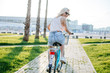 Blonde student girl hurries to classes in summer morning, riding fast on old bicycle along garden footpath.