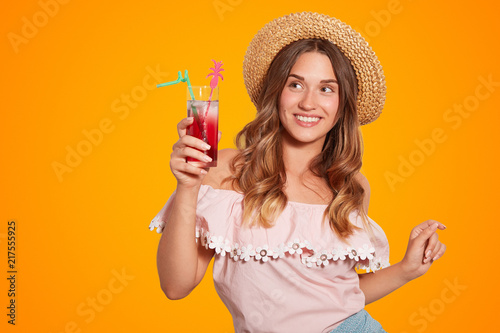 Happy female with positive smile, dressed in summer hat and blouse, holds summer cocktail, enjoys unforgettable rest, has positive expression, isolated over orange background. People, vacation concept