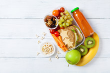 School Lunch Box With Vegetables, Fruits And Sandwich For Healthy Snack On White Wooden Table Top View.