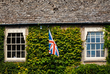 Medieval Cotswold Stone Cottage With British Flag Between Windows In The Village Of Bibury, England
