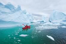 Man Paddling On Kayak Between Ice In Antractica In Iceberg Graveyard, Extreme Winter Kayaking, Polar Adventure Near Pleneau Island
