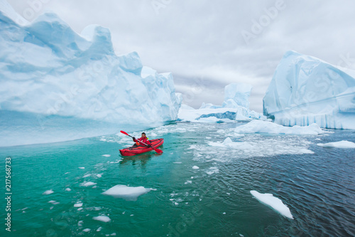 mata magnetyczna man paddling on kayak between ice in Antractica in Iceberg Graveyard, extreme winter kayaking, polar adventure near Pleneau island