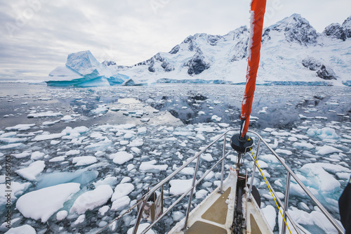 sailing boat in Antarctica, yacht navigation through icebergs and sea ice