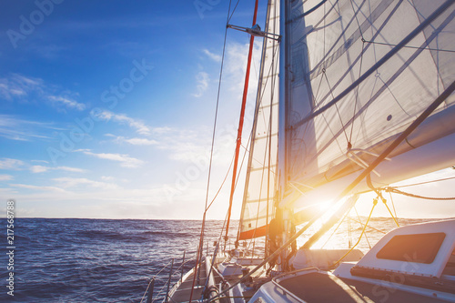 Poster Zeilen sailing boat in open sea at sunset, beautiful luxurious yacht crossing ocean