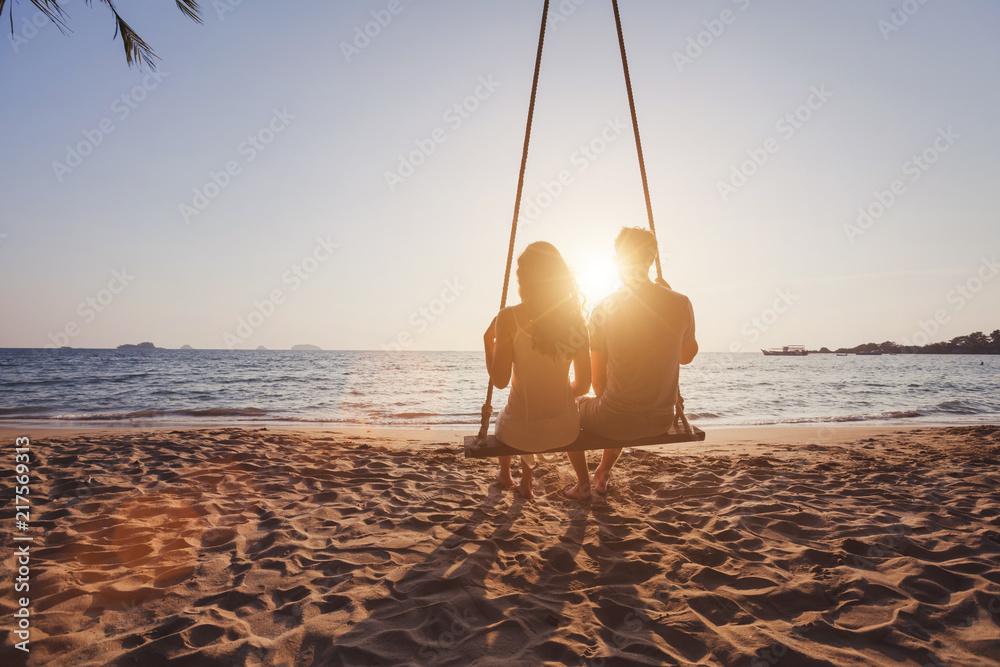 Fototapeta beach holidays for romantic young couple, honeymoon vacations, silhouettes of man and woman sitting together on swing and enjoying sunset