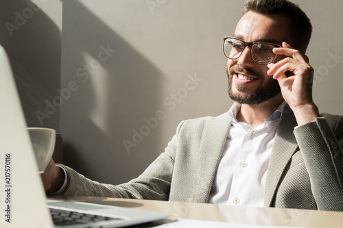 Fotografía  Smiling bearded manager in eyeglasses sitting at the table and looking at laptop