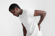 Studio Shot Of Young African American Man Isolated On Grey Background Dressed In T-shirt Keeping Hand On His Back Experiencing Severe Backache, Looking Miserable And Suffering From Pain As It Hurts