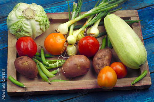 Fotobehang Groenten fresh organic farm vegetables on a wooden tray top view blue wooden boards for background ingredients for vegetable stew vegetarian food concept