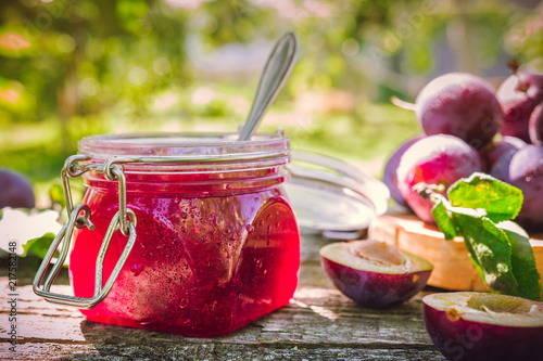 Fotografía  Glass jar with plum jam confiture and ripe plum berries in a basket on a wooden