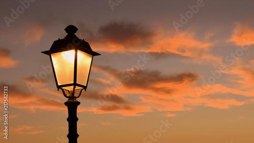 Orange leuchtender Abendhimmel, umrahmt von Zweigen unte antiker Laterne im Hintergrund