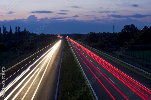 Poster Nacht snelweg Speedway at night, car lights and road with sky and clouds.