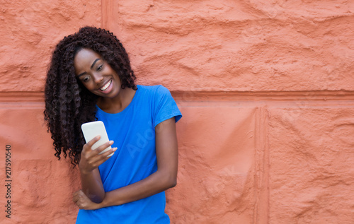 Fotografía  Beautiful african american woman in a blue shirt texting message with mobile pho