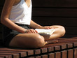 Slim girl reading a book sitting on a wooden bench in a Lotus position. Summer leisure, reading woman, correct posture