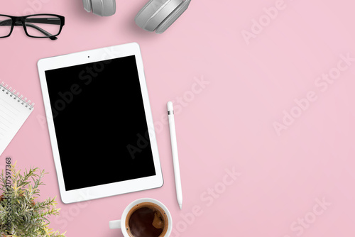 Tablet mockup on pink work desk surrounded with headphones, glasses, notepad, plant, cup of coffee and pen. Free space beside for text. Flat lay composition.