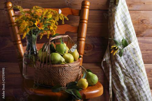 груши в плетеной корзине с букетом цветов и бабочкой